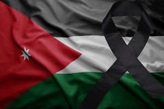 Flag of jordan with black mourning ribbon. Waving national flag of jordan with black mourning ribbon Royalty Free Stock Image