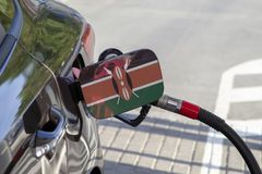 Flag of Kenya on the car`s fuel filler flap. Flag of Kenya on the car`s fuel tank filler flap. Fueling car with petrol pump at a gas station. Petrol station stock photography