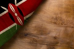 Flag of Kenya from rough fabric. On a wooden background stock photography