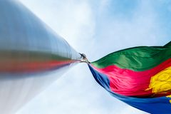 The flag of the Krasnodar Territory is developing in the wind. A massive flagpole with a reflection of the flag royalty free stock photography