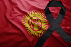 Flag of kyrgyzstan with black mourning ribbon Stock Photo