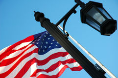 Flag And Lamppost. Angled abstract shot of the American flag and a black lamppost, with a blue sky background royalty free stock images
