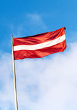 Flag of Latvia above blue sky Stock Photo