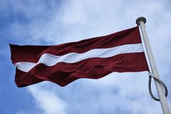 Flag of Latvia flying in breeze. Top of  a flagpole zoomed in to show an unfurled Latvian national flag in a steady breeze against blue sky with white clouds Stock Image