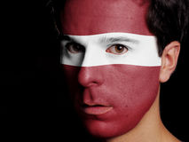 Flag of Latvia. Painted on a Face of a Young Man royalty free stock photo