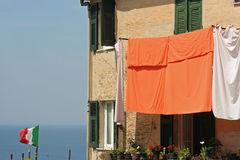 Flag and laundry hung on to dry, Corniglia. Flag and laundry hung on to dry.Corniglia is one of five famous villages of Cinque Terre, suspended between sea and stock photos