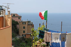 Flag upon laundry hung on to dry, Corniglia. Flag upon laundry hung on to dry.Corniglia is one of five famous villages of Cinque Terre, suspended between sea stock images