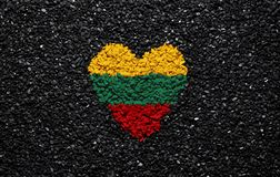 Flag of Lithuania, Lithuanian flag, heart on the black background, stones, gravel and shingle, wallpaper. Flag of Lithuania, the Lithuanian flag, heart on the stock photo