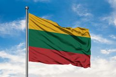 Flag of Lithuania waving in the wind against white cloudy blue sky. Lithuanian flag stock images