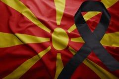 Flag of macedonia with black mourning ribbon. Waving national flag of macedonia with black mourning ribbon Royalty Free Stock Image