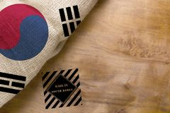 Flag of and made in South Korea. Flag of South Korea made from rough fabric on a wooden background with stamp made in South Korea stock image