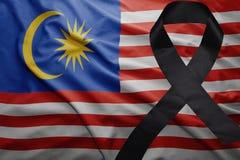 Flag of malaysia with black mourning ribbon. Waving national flag of malaysia with black mourning ribbon Royalty Free Stock Photo