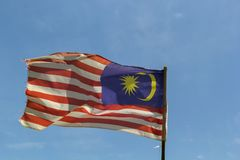 Flag of Malaysia fluttering in the wind against the blue sky. With clouds stock photo