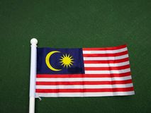 The flag of Malaysia isolated on a dark background. Royalty Free Stock Image
