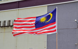 Flag of Malaysia waving in the air with typical building in the background Royalty Free Stock Image