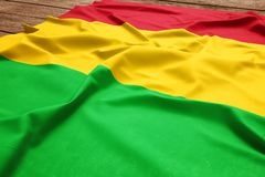 Flag of Mali on a wooden desk background. Silk Malian flag top view.  royalty free stock images