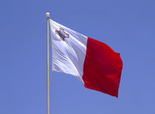 Flag of Malta. The national flag of the island Republic of Malta - proudly displaying the George Cross awarded to Malta in 1942 for Gallantry shown in WWII Royalty Free Stock Photo