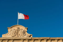 Flag of Malta. The coat of arms of Castille and Leon on top of the Auberge de Castille Office of Prime Minister, Valetta Royalty Free Stock Photography