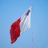 The flag of Malta fluttering over the Post of Castile in Birgu. The bi-colour flag of Malta flaps over the Post of Castile in Birgu, Malta Royalty Free Stock Photos