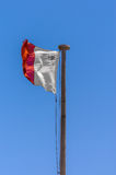 Flag of Malta. Maltese flag on the blue sky waving in the wind Stock Image