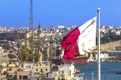 Flag of Malta. Maltese flag on the blue sky waving in the wind and panoramic view of the Maltese capital, Valletta, Malta Stock Photo