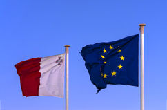 Flags of the EU and Malta. Maltese and EU flags next to each other on the blue sky waving in the wind, Valletta, Malta Royalty Free Stock Photography