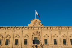Flag of Malta. Valletta, Malta. Flag of Malta. The coat of arms of Castille and Leon on top of the Auberge de Castille Office of Prime Minister, Valletta Royalty Free Stock Image