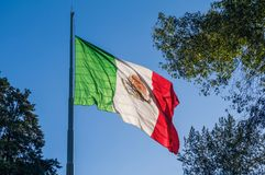 Flag of Mexico waving on a flagpole. A Mexican flag waves majestically on top of a flagpole located in the Luis G. Urbina Park, popularly known as the Sunken royalty free stock image