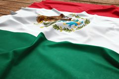Flag of Mexico on a wooden desk background. Silk Mexican flag top view stock photos