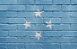 Flag of Micronesia on brick wall. Flag of the Federated States of Micronesia painted onto a grunge brick wall Royalty Free Stock Photos