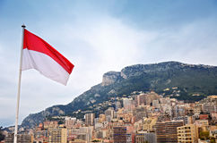 The flag of Monaco and city in the background. Photo of the flag of Monaco and city in the background Royalty Free Stock Photo