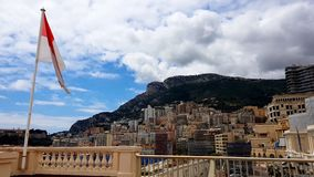 Flag of Monaco fluttering against background of mountain and resort cityscape. Stock photo royalty free stock photography