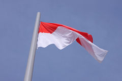 Flag of Monaco. Over blue sky Stock Image