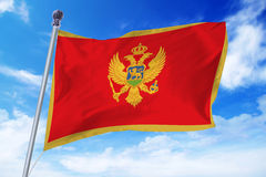 Flag of Montenegro developing against a blue sky. Flag of Montenegro developing against a clear blue sky royalty free stock image