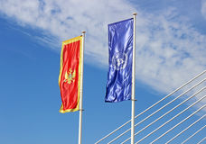 The flag of Montenegro and the UN flag. On a blue background Stock Image