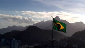 A flag and a monument. A view of Christ Redeemer from the fort of Leme, Rio de Janeiro, Brazil with the Brazilian flag in front of Stock Image