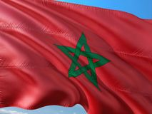 Flag of Morocco waving in the wind against deep blue sky. High quality fabric stock photo