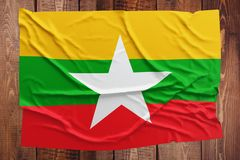 Flag of Myanmar - Burma on a wooden table background. Wrinkled Burmese flag top view.  royalty free stock image