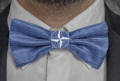 Flag of Nato Organization on bowtie business man suit. Close royalty free stock photos