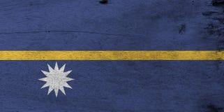 Flag of Nauru on wooden plate background. Grunge Nauruan flag texture. stock photo
