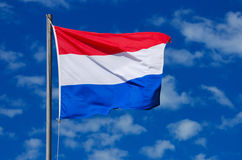 Flag of the Netherlands. The national flag of the Netherlands in red, white and blue waving in the wind in front of blue sky background Royalty Free Stock Image