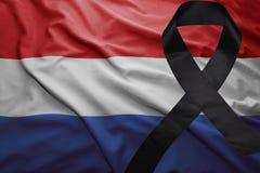 Flag of netherlands with black mourning ribbon. Waving national flag of netherlands with black mourning ribbon Royalty Free Stock Photos