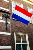 Crown sky holiday house wall flag Netherlands building King`s Day Holland dutch celebration april. The flag of the Netherlands on a building during King`s Day Stock Images