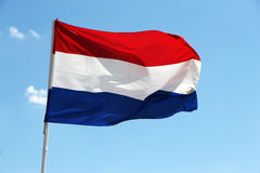 Flag of netherlands. A close up view of a flag of netherlands, against a bright blue sky, landscape cut Royalty Free Stock Photography