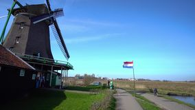 Zaanse Schans windmill add flag near the field and road. The flag of the Netherlands is set near the old windmill on a vast field near the asphalt road in Zaanse stock footage
