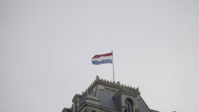 Flag of netherlands on the top  building in front  the cloudy sky Stock Image
