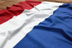 Flag of Netherlands on a wooden desk background. Silk Dutch flag top view.  royalty free stock photo