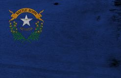 Flag of Nevada on wooden plate background. Grunge Nevada flag texture, The states of America. Solid cobalt blue field. The canton contains two sagebrush stock image