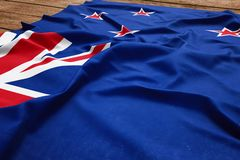 Flag of New Zealand on a wooden desk background. Silk Kiwi flag top view royalty free stock photos
