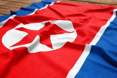 Flag of North Korea on a wooden desk background. Silk North Korean flag top view stock image